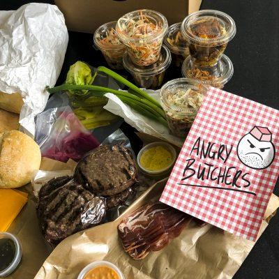 """""""De Angry Butchers Box is een echte aanrader! Na ontvangst van een fantastische mail kwam een super vriendelijke bezorger onze box brengen!! Kwade slager Wannes was in een zeer goeie bui 🤣 Topkwaliteit van vlees, mega lekkere broodjes en zalige toppings! Hopelijk komen jullie snel terug naar Aalst! 😋 😋 😋"""" Elien. D.G. 11/03/2021"""